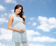 Happy pregnant woman touching her big belly Stock Image