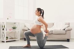 Happy pregnant woman training yoga at home. Motherhood, active pregnancy, happiness, training, yoga concept Stock Photography
