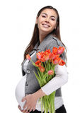 Happy pregnant woman with tulips Royalty Free Stock Photography