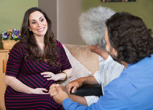 Happy Pregnant Woman with Two Men Stock Photography
