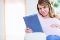 Happy pregnant woman using tablet Royalty Free Stock Photos