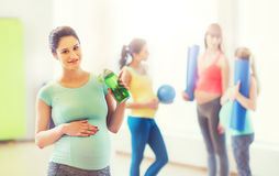 Happy pregnant woman with water bottle in gym Stock Image