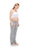 Happy pregnant woman weighting herself Stock Image