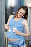 Happy pregnant woman with white baby booties Stock Photos