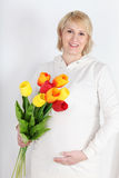 Happy pregnant woman in white with bouquet of tulips Royalty Free Stock Image
