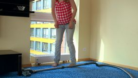 Happy pregnant woman work with vacuum cleaner and sit on radiator to relax stock video