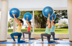 Happy pregnant women exercising with ball in gym. Pregnancy, sport, fitness, people and healthy lifestyle concept - group of happy pregnant women exercising with Stock Images