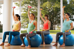 Happy pregnant women exercising on fitball in gym Stock Photos