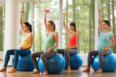 Happy pregnant women exercising on fitball in gym Stock Images