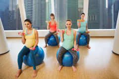 Happy pregnant women exercising on fitball in gym Stock Photography