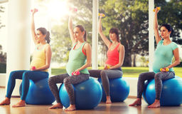Happy pregnant women exercising on fitball in gym Royalty Free Stock Images
