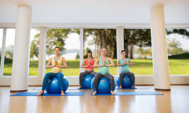 Happy pregnant women exercising on fitball in gym Royalty Free Stock Image