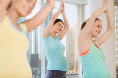 Happy pregnant women exercising in gym Stock Image