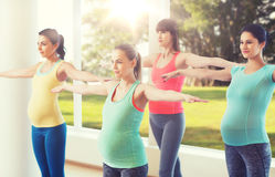 Happy pregnant women exercising in gym Stock Photos