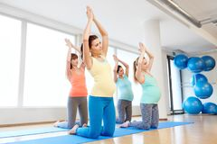 Happy pregnant women exercising on mats in gym royalty free stock photos