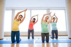 Happy pregnant women exercising on mats in gym. Pregnancy, sport, fitness, people and healthy lifestyle concept - group of happy pregnant women exercising on Royalty Free Stock Photos