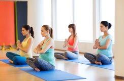 Happy pregnant women exercising yoga in gym Stock Photos