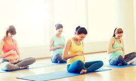 Happy pregnant women exercising yoga in gym Royalty Free Stock Images