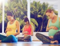 Happy pregnant women exercising yoga in gym Royalty Free Stock Photos