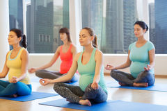 Happy pregnant women exercising yoga in gym Stock Images