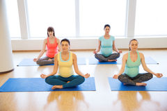 Happy pregnant women exercising yoga in gym. Pregnancy, sport, fitness, people and healthy lifestyle concept - group of happy pregnant women exercising yoga and Royalty Free Stock Image