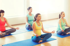Happy pregnant women exercising yoga in gym Stock Image