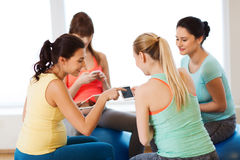 Happy pregnant women with gadgets in gym Stock Image