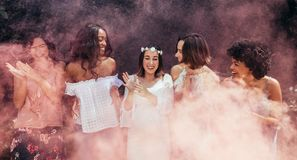 Pregnant woman enjoying baby shower outdoors with best friends. Happy pregnant women and her friends with smoke grenade standing outdoors. Happy young expecting Stock Image
