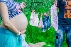 Happy pregnant women with husband outdoor in the garden Stock Photos