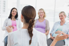 Happy pregnant women listening to gesturing doctor at antenatal class Stock Photo