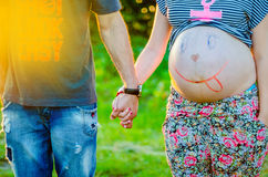 Happy pregnant women outdoor in the garden holding hands with hu Royalty Free Stock Photography