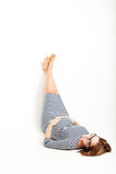 Happy pregnant women rests on floor legs up Stock Photos