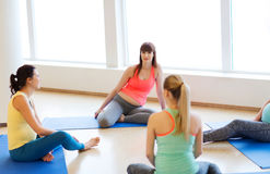 Happy pregnant women sitting on mats in gym Royalty Free Stock Image