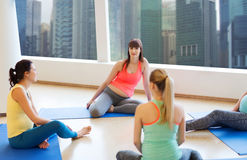 Happy pregnant women sitting on mats in gym Stock Photos