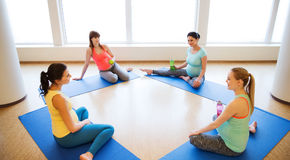 Happy pregnant women sitting on mats in gym Royalty Free Stock Images