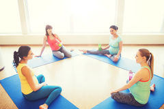 Happy pregnant women sitting on mats in gym Stock Photo