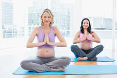 Happy pregnant women in yoga class in lotus pose Stock Photos