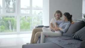 Happy pregnant, young female with excitement tells male about pregnancy and puts hands on belly and future parent smiles. Happily sitting on couch at home stock footage