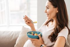 Happy pregnant young woman having healthy breakfast stock image