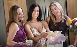 Happy Prenant Woman. Happy pregnant women shares new baby clothes with two friends in kitchen Royalty Free Stock Photo