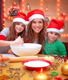 Happy preparing to Christmas. Portrait of cheerful young family preparing to Christmas dinner, mother with two kids cooking at home wearing Santa hat Stock Photo