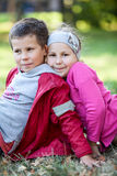 Happy preschool brother and sister sitting together in summer park Royalty Free Stock Images