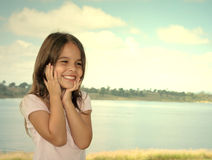 Happy preschool girl. Holding face with sea in background royalty free stock images