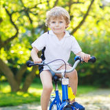 Happy preschool kid boy having fun with riding his bicycle Stock Photo