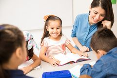Happy preschool student enjoying class. Portrait of a beautiful Hispanic preschool student enjoying her day at school and doing a writing exercise royalty free stock images