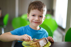 Happy preschooler boy eating cake in confectionery Stock Photography