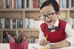 Happy preschooler at library. A preschooler boy is enjoying his study at the library Stock Image