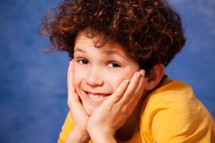 Happy curly-haired boy resting chin on hands. Happy preteen boy with curly hair resting chin on hands and looking at camera Royalty Free Stock Photo
