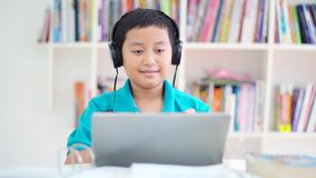 Happy preteen boy listening music in library. Happy preteen boy listening music with headphones and laptop computer in the library stock video footage