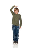 Happy preteen boy pointing measuring what has grown Royalty Free Stock Photo